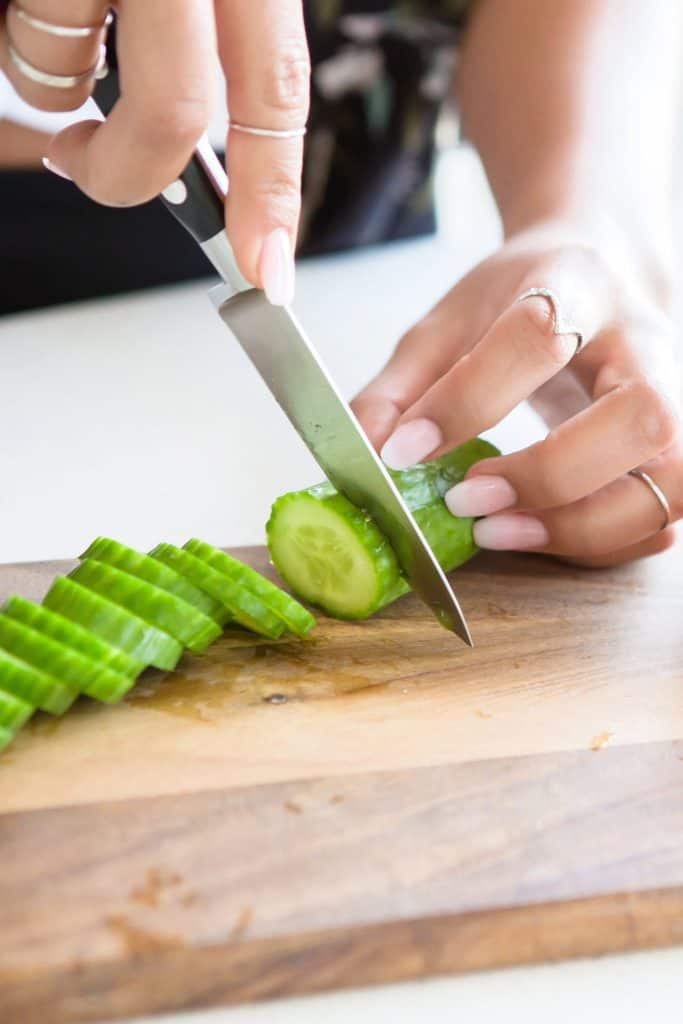 woman slicing up a cucumber
