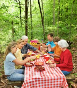 family eating outside on picnic table