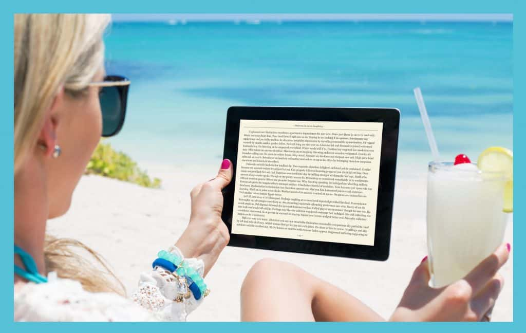 Woman reading a kindle e-reader on the beach.