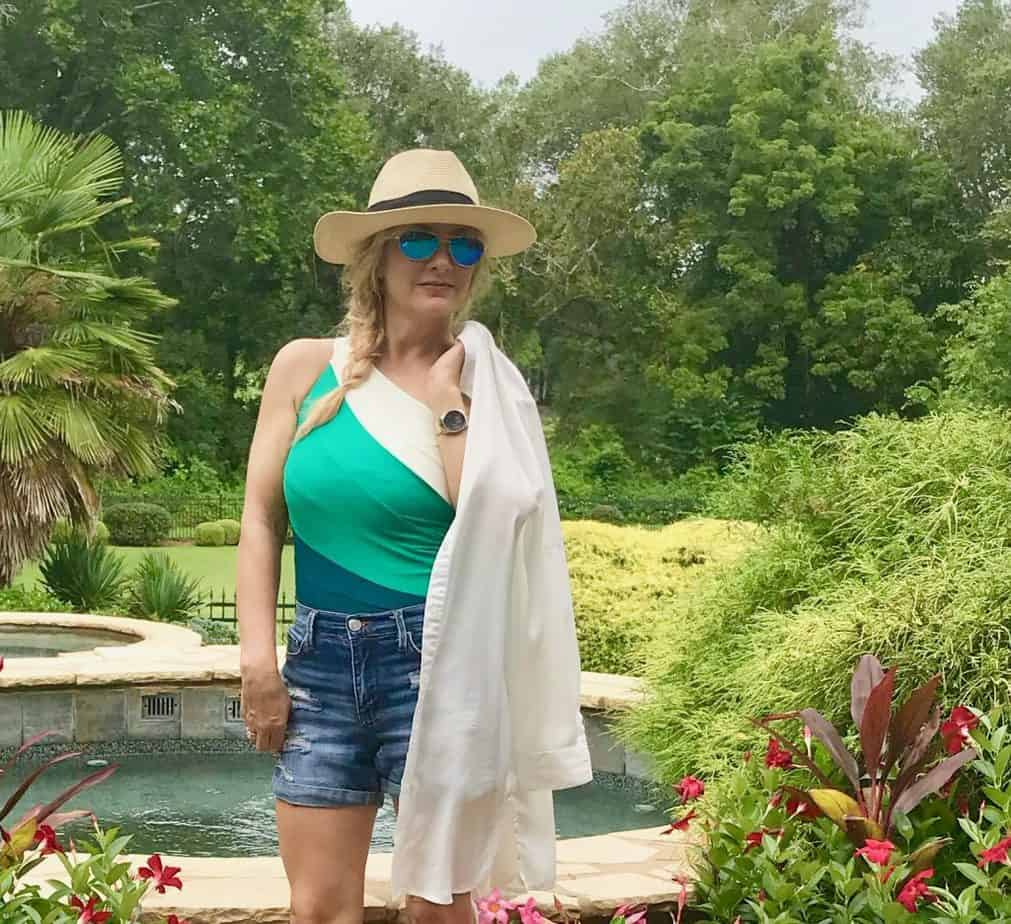 Jen wearing hat, sunglasses, swimsuit cover-up, jeans shorts