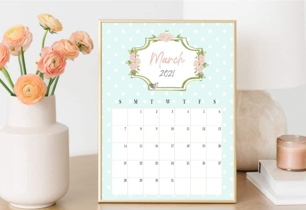 March 2021 calendar on a desk next to flowers.