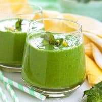 Healthy keto green smoothies in two glasses with straws.