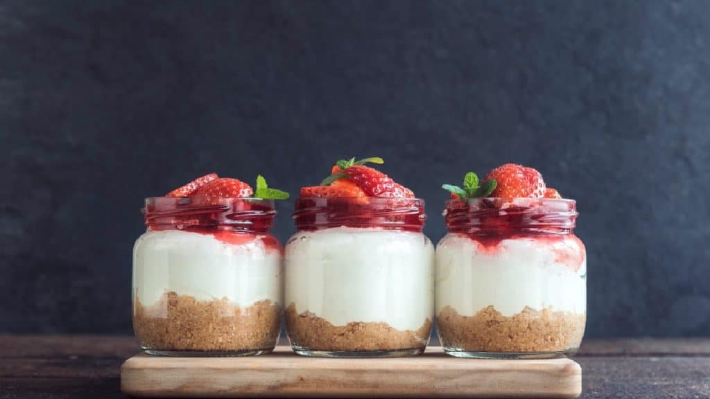 Three low-carb cheesecake servings in glass jars.