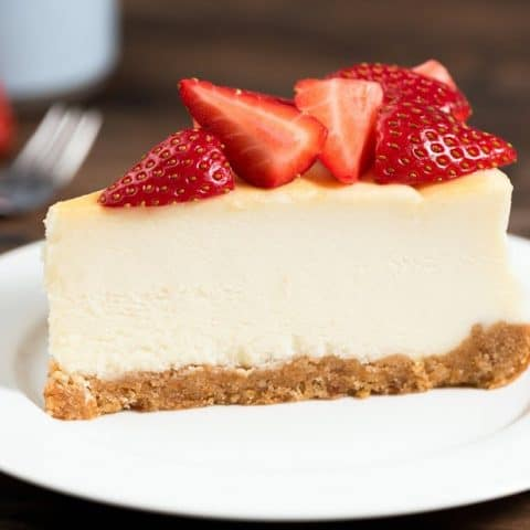Keto cheesecake with strawberries on a white plate.