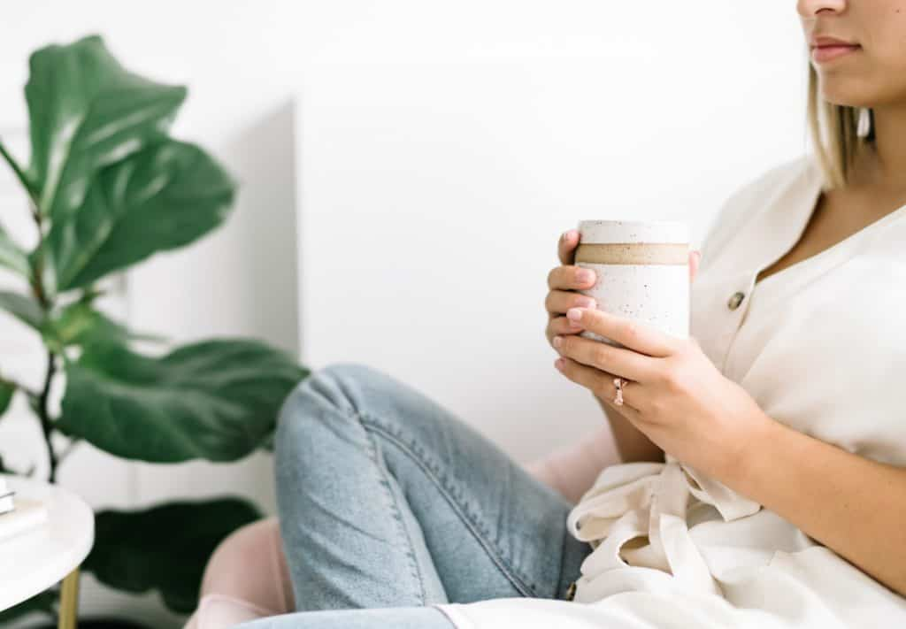 woman drinking coffee on couch at home