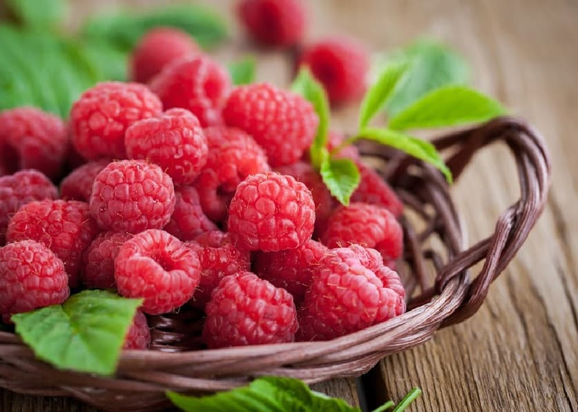 Red raspberries sitting in a basket on a table.