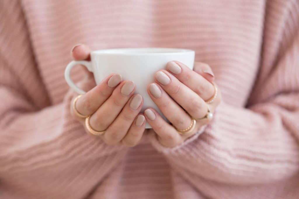 Woman holding a mug of coffee.